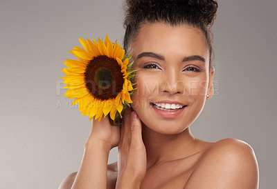 Buy stock photo Studio portrait of a beautiful young woman posing with a sunflower against a grey background