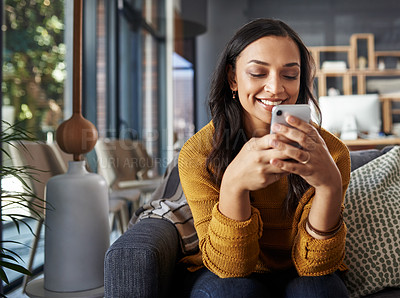 Buy stock photo Shot of a beautiful young woman using her cellphone while relaxing on a couch at home