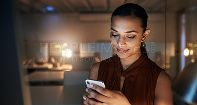 Buy stock photo Shot of a beautiful young businesswoman using her cellphone while working late in her office during the evening