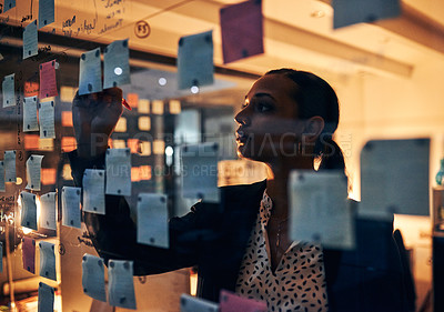 Buy stock photo Shot of a young businesswoman writing adhesive notes on a glass wall while working late in her office