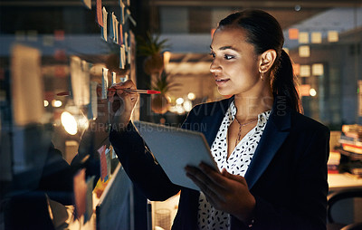 Buy stock photo Shot of a young businesswoman writing adhesive notes on a glass wall while walking late in her office
