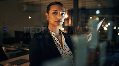 Buy stock photo Portrait of a beautiful young businesswoman using a digital tablet while working late in her office during the evening