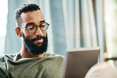 Buy stock photo Shot of a handsome young man using his digital tablet while sitting on a sofa at home