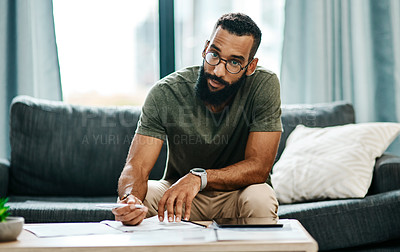 Buy stock photo Shot of a young man going over his finances at home