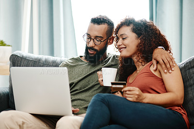 Buy stock photo Shot of a young couple using a credit card and laptop on the sofa at home