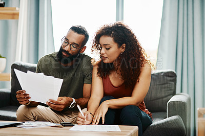 Buy stock photo Shot of a young couple going over their finances together at home