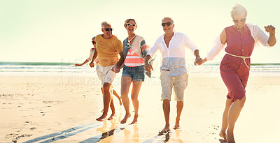 Buy stock photo Full length shot of a group of senior friends enjoying their day out on the beach