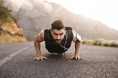Buy stock photo Portrait of a sporty young man doing pushups while exercising outdoors