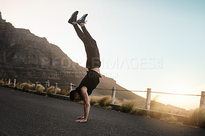 Buy stock photo Shot of a sporty young man doing a handstand while exercising outdoors