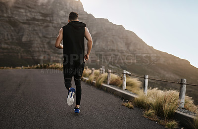 Buy stock photo Rearview shot of a sporty young man exercising outdoors