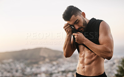 Buy stock photo Shot of a sporty young man wiping the sweat from his forehead with his top while exercising outdoors