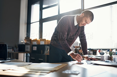 Buy stock photo Shot of a mature businessman writing notes while working in an office