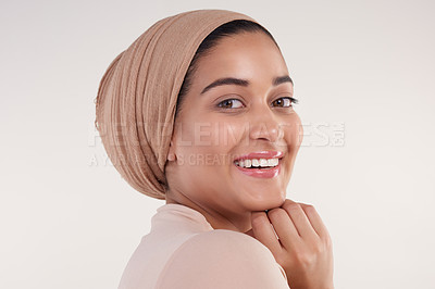 Buy stock photo Studio shot of a young attractive woman smiling over her shoulder at the camera against a beige background
