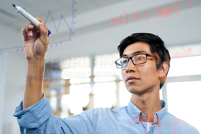 Buy stock photo Shot of a young businessman writing notes on a glass wall in an office