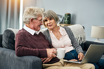 Buy stock photo Cropped shot of an affectionate senior couple using a laptop while sitting on their living room sofa at home