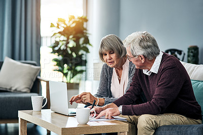Buy stock photo Cropped shot of a senior couple going over the household budget while sitting on their living room sofa at home