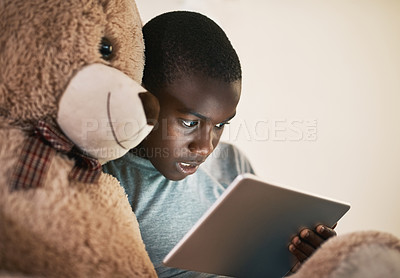 Buy stock photo Shot of a young boy using a digital tablet at night in bed