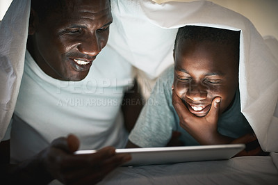 Buy stock photo Shot of a young boy using a digital tablet with his father at night in bed