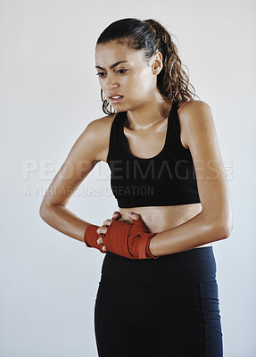 Buy stock photo Shot of a young sportswoman suffering from abdominal pain while working out indoors