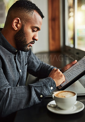 Buy stock photo Cropped shot of a handsome young man using a digital tablet while sitting in a coffeeshop