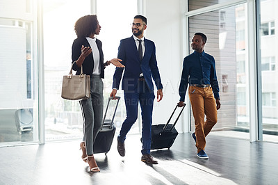 Buy stock photo Full length shot of a group of businesspeople walking with their travel bags inside a building