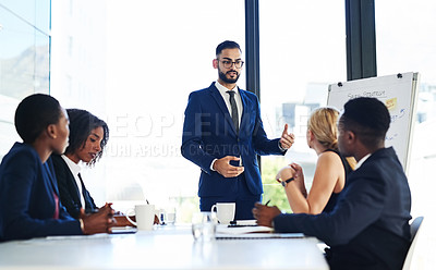 Buy stock photo Shot of a handsome young businessman using a whiteboard to explain an idea to his colleagues during a meeting