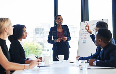 Buy stock photo Shot of an attractive young businesswoman using a whiteboard to explain an idea to her colleagues during a meeting