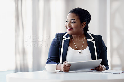 Buy stock photo Cropped shot of an attractive young businesswoman looking thoughtful while working on her tablet in the office