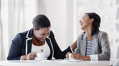 Buy stock photo Cropped shot of two attractive young businesswomen having a laugh while working together in their office