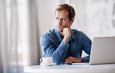 Buy stock photo Cropped shot of a handsome mature businessman looking thoughtful while working on his laptop in the office