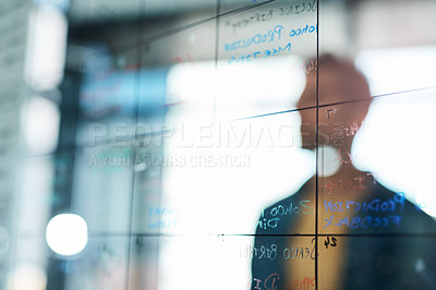 Buy stock photo Shot of a businessman brainstorming with notes on a glass wall in an office