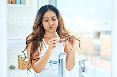 Buy stock photo Shot of a beautiful young woman looking frustrated while looking at her hair