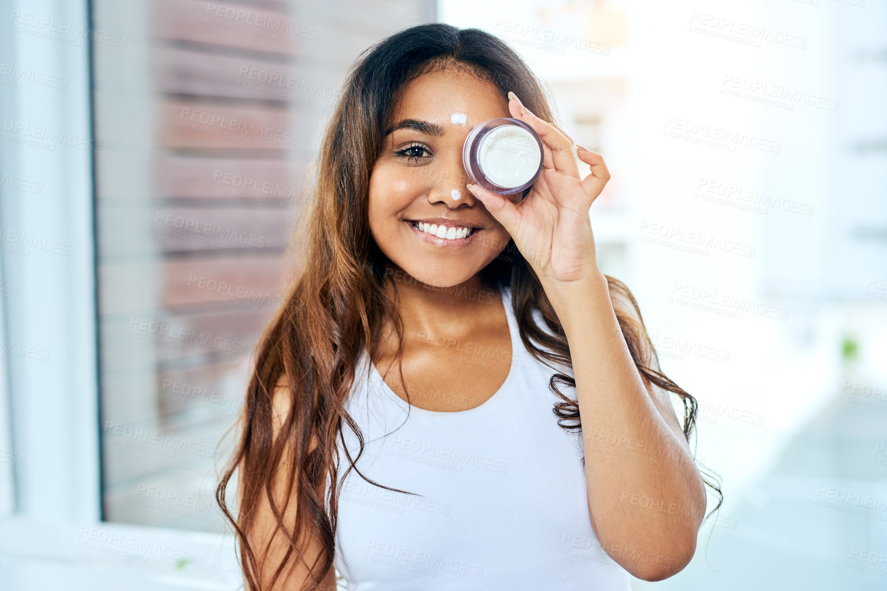 Buy stock photo Shot of a beautiful young woman covering her eye with a moisturizer container
