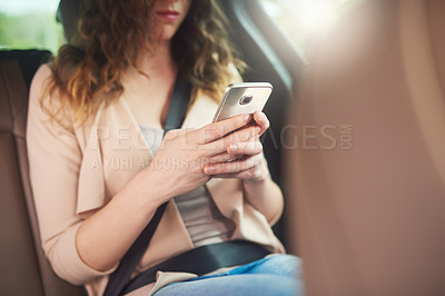 Buy stock photo Shot of an unrecognizable businesswoman using her cellphone while travelling in the backseat of a car