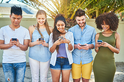 Buy stock photo Cropped shot of a group of cheerful young friends texting on their cellphones outside in the afternoon