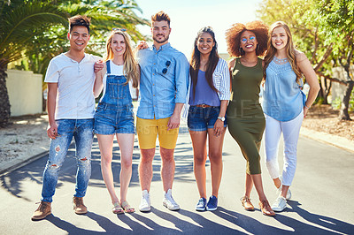 Buy stock photo Portrait of a group of cheerful young friends standing arms around outside in the afternoon