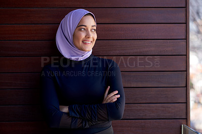 Buy stock photo Cropped shot of an attractive young woman wearing a headscarf and posing with her arms crossed against a wooden background