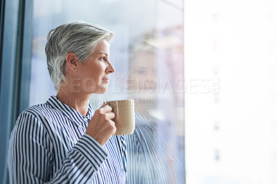 Buy stock photo Shot of an attractive mature businesswoman drinking coffee while looking out of her office window