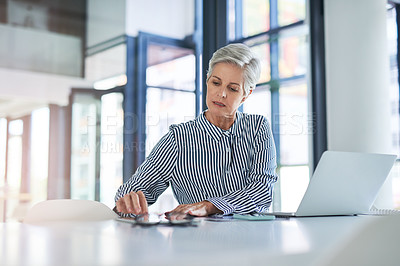 Buy stock photo Shot of a mature businesswoman using a digital tablet at her office desk at work