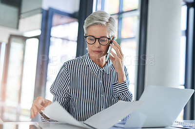 Buy stock photo Shot of an attractive mature businesswoman  handling paperwork while taking a phone call at her office desk at work
