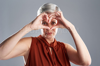 Buy stock photo Portrait of an attractive mature woman making a heart shape with her hands against a grey background