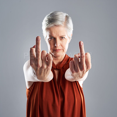 Buy stock photo Portrait of mature woman showing the middle finger against a grey background