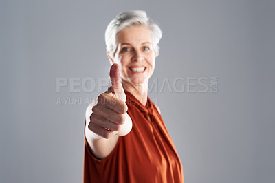 Buy stock photo Portrait of an attractive mature businesswoman posing with her thumbs up against a grey background