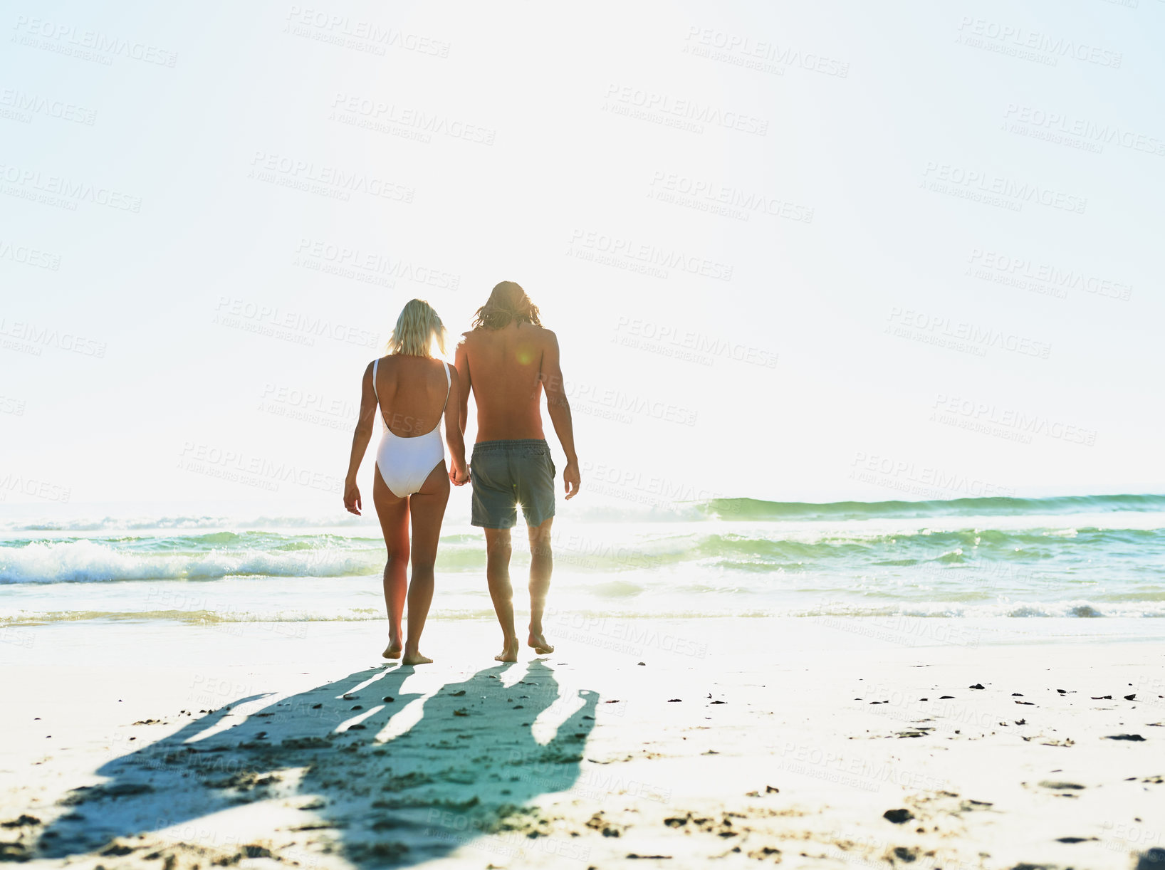 Buy stock photo Rearview shot of a young couple enjoying some quality time together at the beach