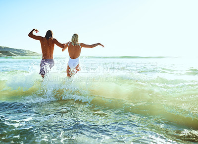 Buy stock photo Rearview shot of a young couple having fun at the beach