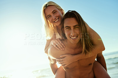 Buy stock photo Portrait of a young man giving his girlfriend a piggyback ride at the beach
