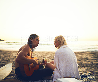 Buy stock photo Rearview shot of a young affectionate couple serenading each other during a date on the beach at sunset