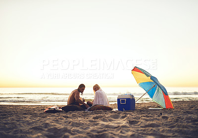 Buy stock photo Shot of an affectionate young couple having a picnic date on the beach at sunset