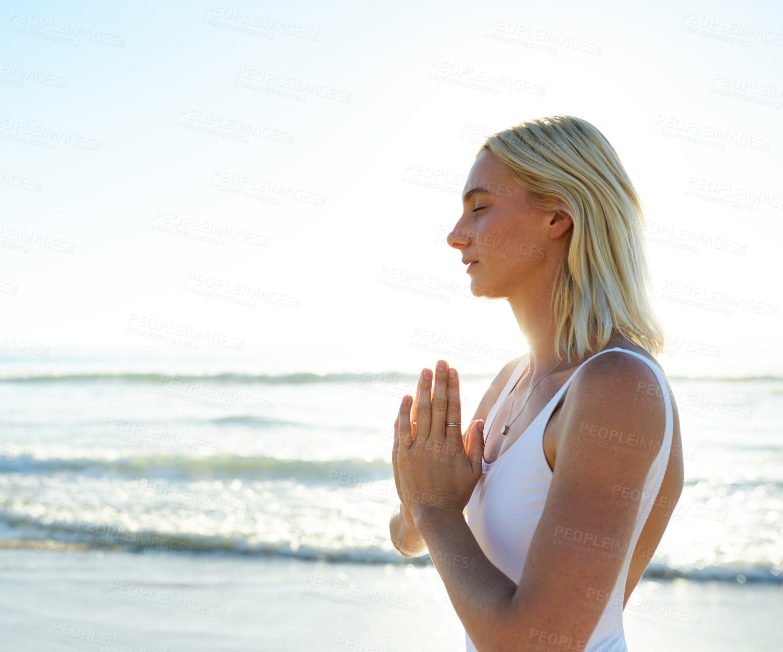 Buy stock photo Cropped shot of an attractive young woman meditating early in the morning on the beach
