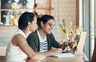 Buy stock photo Shot of young business partners sitting and working with each other in a coffee shop during the day